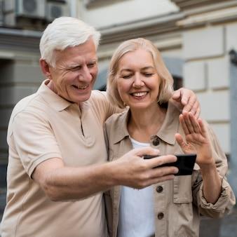 Feliz pareja senior teniendo una llamada de vista mientras está en la ciudad