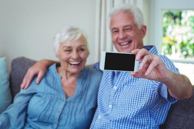 Feliz pareja senior tomando selfie