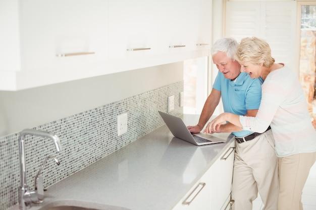 Feliz pareja senior usando laptop en cocina