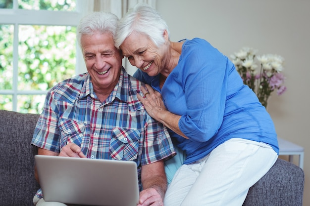 Feliz pareja senior usando laptop