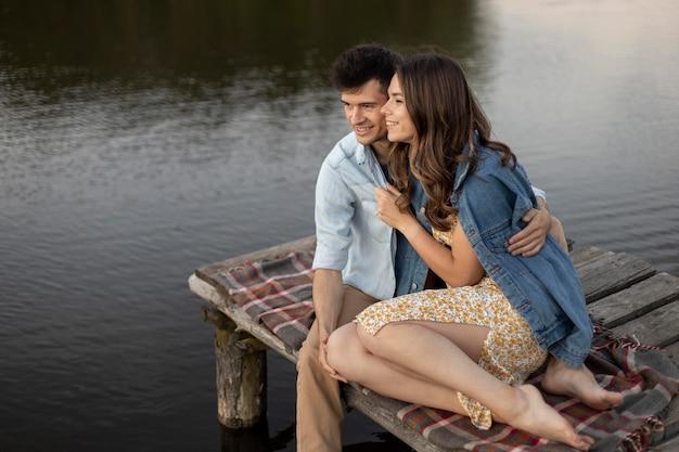 Feliz pareja sentada junto al lago full shot