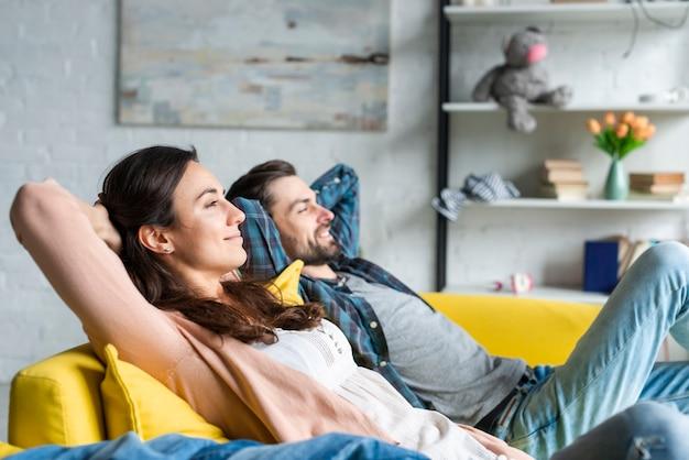 Feliz pareja sentada en el sofá