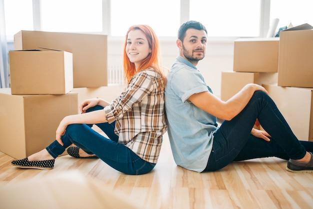 Feliz pareja sentada en el suelo de espaldas entre sí entre cajas de cartón, mudarse a casa nueva, inauguración de la casa
