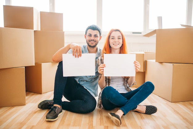 Feliz pareja sentada en el suelo con hojas de papel vacías en las manos, mudarse a casa nueva, inauguración de la casa