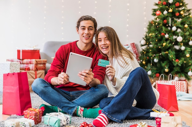 Feliz pareja sentada con tableta en el piso