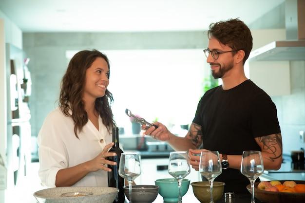 Feliz pareja sirviendo la cena y abriendo una botella de vino