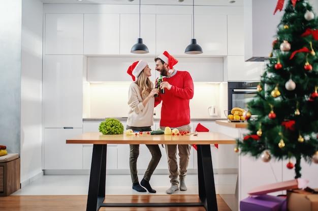 Feliz pareja con sombreros de santa en las cabezas brindando con cerveza mientras está de pie en la cocina en nochebuena