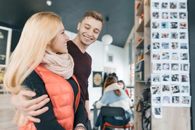 Feliz pareja sonriente abrazando en cafetería
