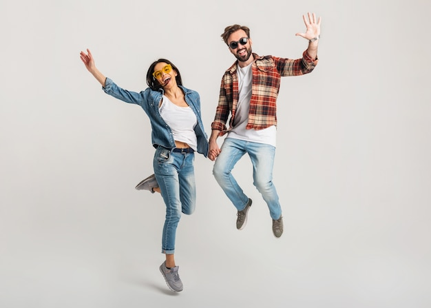 Feliz pareja sonriente aislado saltando activo en estudio blanco