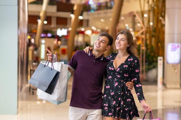Una feliz pareja sonriente camina por el centro comercial en un abrazo con grandes bolsas de compras, el chico señala a la chica algo, ella sonríe. buena compra. descuentos viernes negro
