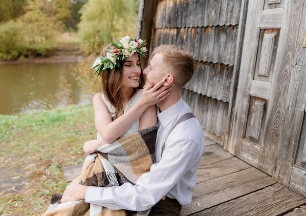 Feliz pareja sonriente cerca de la puerta de una casa de madera cerca del río está sentado y mirando el uno al otro