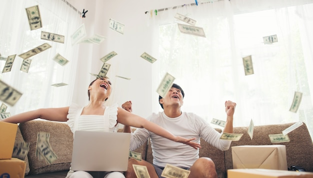 Feliz pareja sonriente exitosa sentado bajo la lluvia de dinero. concepto de negocio en linea