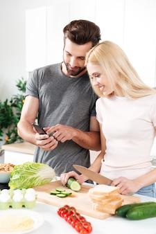 Feliz pareja sonriente con teléfono móvil para encontrar una receta