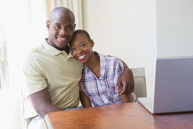 Feliz pareja sonriente usando su computadora portátil en casa