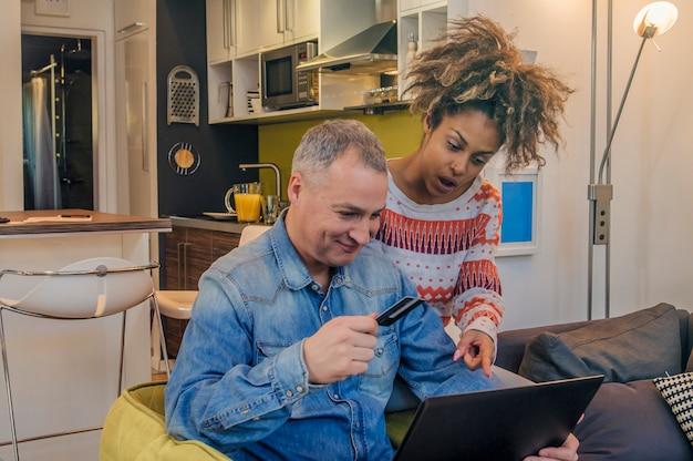Feliz pareja sorprendida buscando y comprando en línea con tarjeta de crédito en casa, compras en línea, la gente compra nuevo regalo de comercio electrónico sitio web
