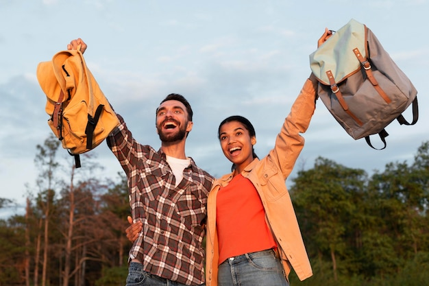 Feliz pareja sosteniendo sus mochilas