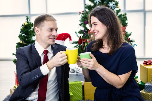 Feliz pareja sosteniendo tazas de café