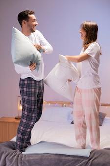 Feliz pareja teniendo una pelea de almohadas
