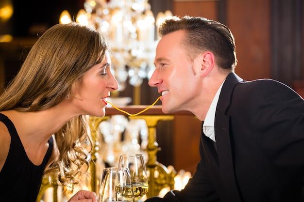 Feliz pareja tiene una cita romántica restaurante de alta cocina comen espagueti, una gran lámpara de araña