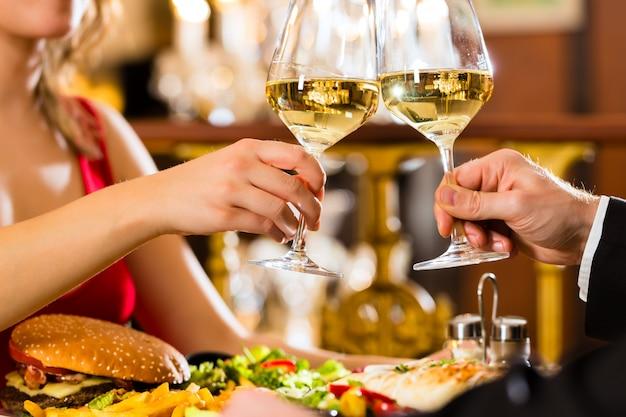 Feliz pareja tiene una cita romántica restaurante gourmet beben vino y vasos tintineantes, aplausos, una gran lámpara de araña
