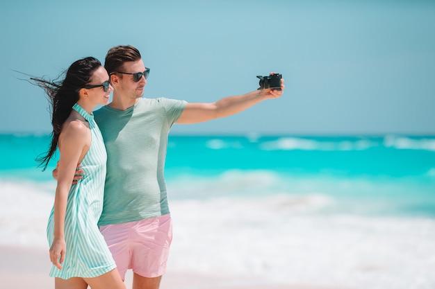 Feliz pareja tomando una foto en la playa blanca en vacaciones de luna de miel