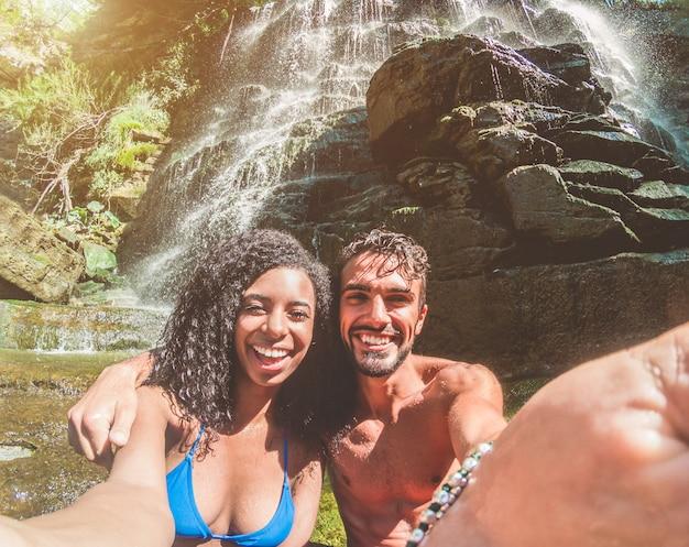 Feliz pareja tomando foto selfie con la cámara del teléfono inteligente bajo cascadas tropicales en vacaciones de verano