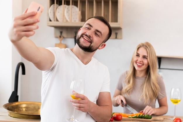 Feliz pareja tomando un selfie en la cocina