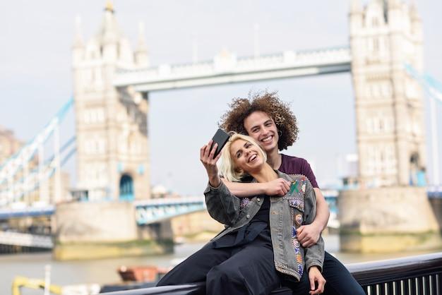 Feliz pareja tomando selfie fotografía en el tower bridge