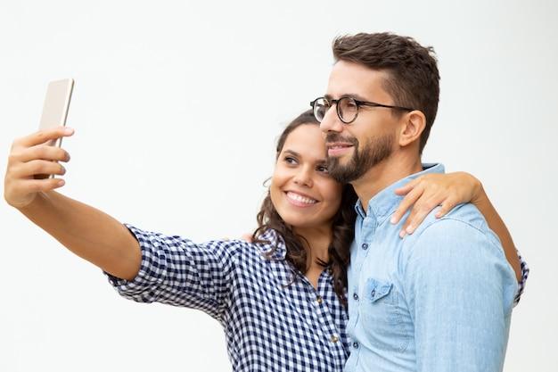 Feliz pareja tomando selfie con smartphone