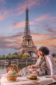 Feliz pareja tomando vino con la vista de la torre eiffel