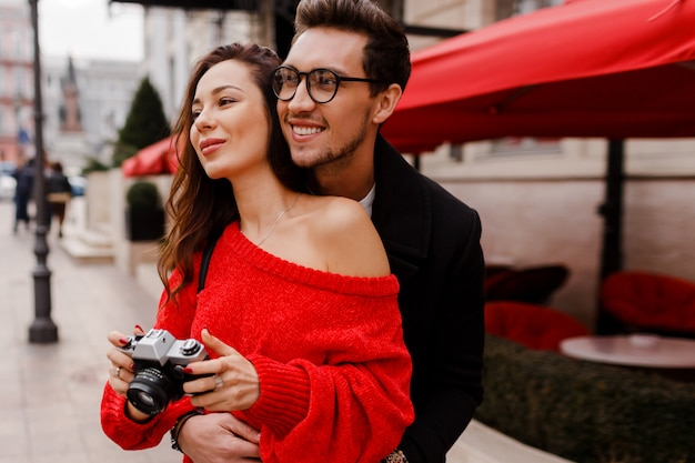 Feliz pareja de turistas avergonzado y posando en la calle de vacaciones. estado de ánimo romántico. hermosa mujer morena con cámara de película.