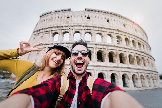 Feliz pareja de turistas divirtiéndose tomando un selfie frente al coliseo de roma. la gente viaja a roma, italia.