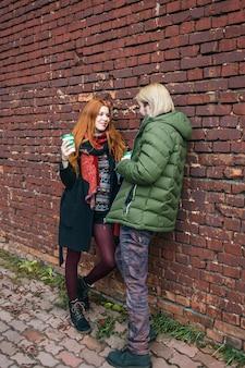 Feliz pareja de turistas en ropa urbana cálida de pie con tazas desechables de café en la pared de ladrillo