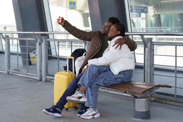 Feliz pareja de turistas toman selfie en el aeropuerto