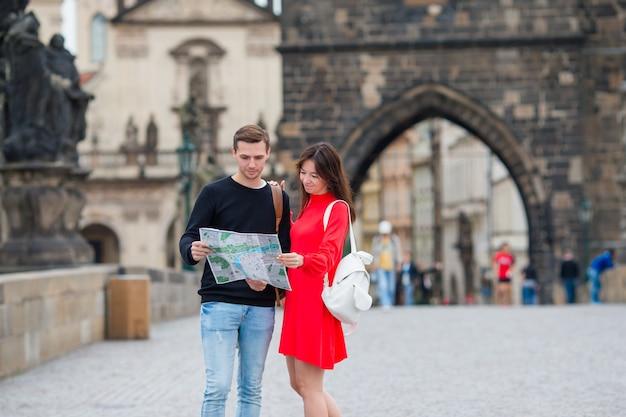 Feliz pareja de turistas viajando por el puente de carlos en praga en lugares famosos con mapa de la ciudad