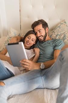 Feliz pareja usando tableta en la cama