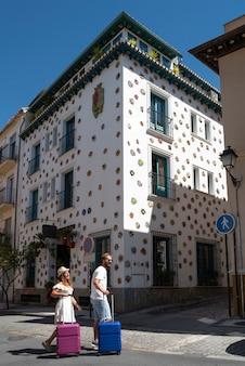 Feliz pareja de vacaciones con maletas en un pueblo andaluz con arquitectura típica y colorida