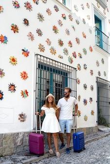 Feliz pareja de vacaciones con maletas en un pueblo andaluz