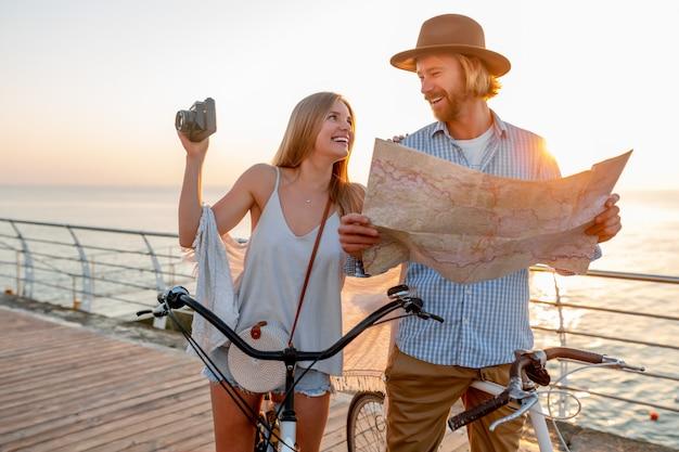 Feliz pareja viajando en verano en bicicleta, mirando en el mapa haciendo turismo y tomando fotos