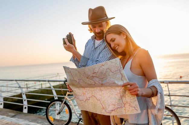 Feliz pareja viajando en verano en bicicleta, mirando un mapa y tomando fotos con la cámara