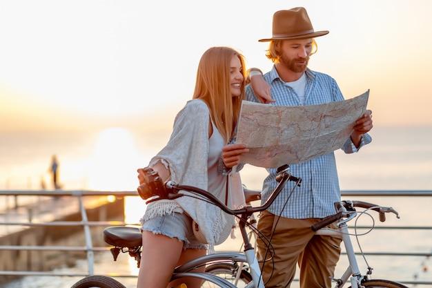 Feliz pareja viajando en verano en bicicleta, mirando en el mapa de turismo