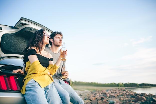Feliz pareja de viajeros sentado en el maletero del coche y ver el amanecer y beber cerveza.