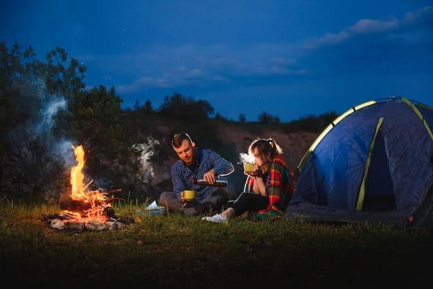 Feliz pareja de viajeros sentados junto a la fogata y la carpa turística brillante