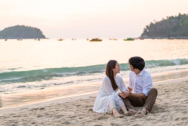 Feliz pareja va viajes de luna de miel en la playa de arena tropical en verano
