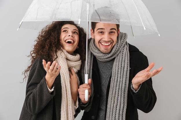 Feliz pareja vistiendo ropa de otoño de pie bajo un paraguas aislado sobre pared gris