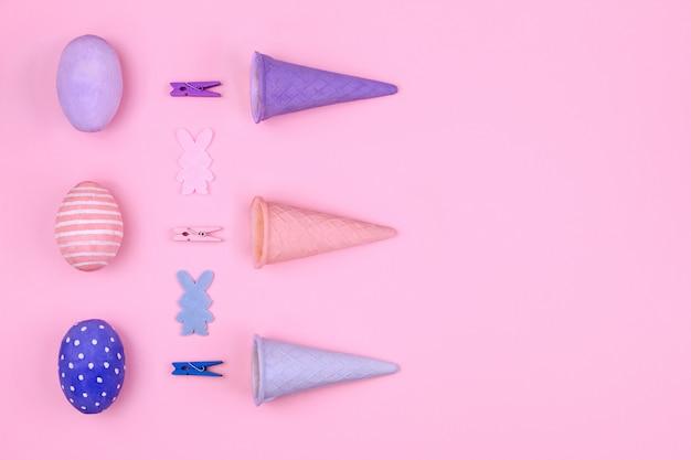 Feliz pascua. huevos de pascua de color rosa, azul y violeta, pinza para la ropa colorida, cono de waffle y silueta de conejo sobre fondo rosa