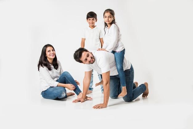 Feliz paseo loco en la espalda del padre. niña india sentada en la espalda de papá mientras la madre y el hermano se ríen. enfoque selectivo