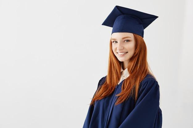 Feliz pelirroja mujer graduada sonriendo.