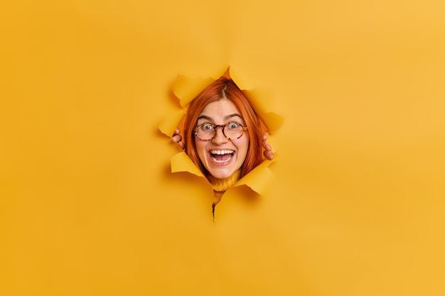 Feliz pelirroja sorprendida mujer caucásica mira con amplia sonrisa reacciona en algo muy bueno usa gafas ópticas mira a través del orificio de papel