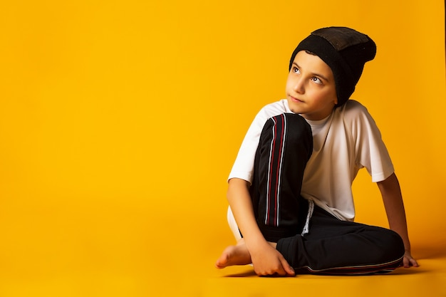 Feliz pequeña bailarina de hip-hop - niño bailando aislado sobre fondo amarillo. b-boy blanco joven bailando break dance.